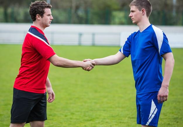 Voetballers in blauwe en rode handen schudden
