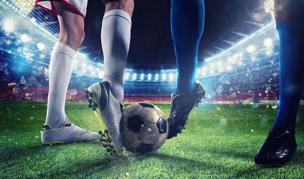 Voetballers met soccerball in het verlichte stadion tijdens de wedstrijd