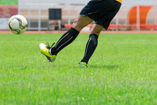 Voetballers oefenen met voetballen op het grasveld.