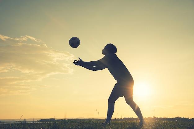 Voetballersmens die achterdiemening in silhouet bevinden op zonsondergangachtergrond wordt geïsoleerd