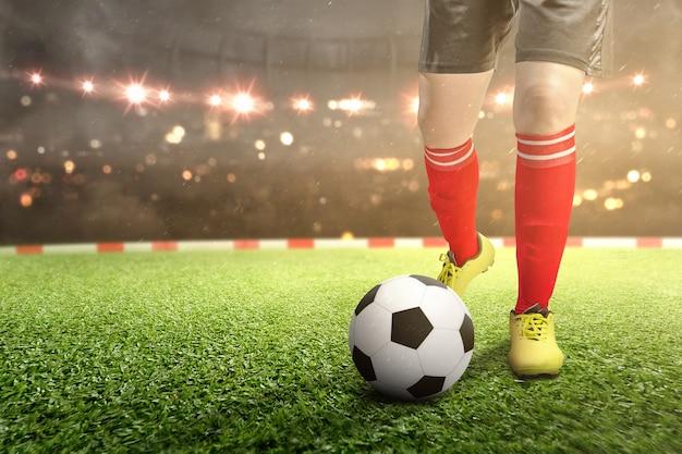 Voetballervrouw die de bal op het voetbalgebied schoppen