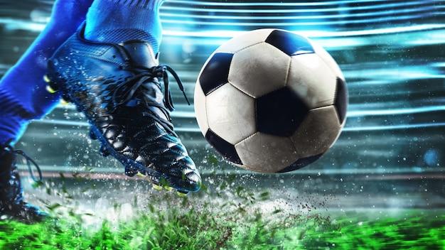 Voetbalscène bij nachtgelijke met close-up van een voetbalschoen die de bal met macht raakt