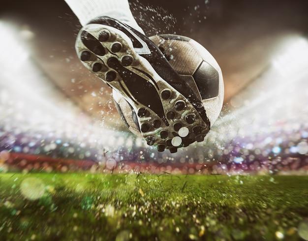Voetbalscène bij nachtwedstrijd met close-up van een voetbalschoen die de bal met kracht raakt