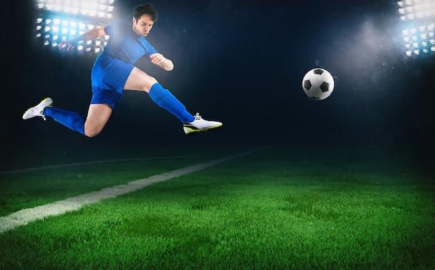 Voetbalscène bij nachtwedstrijd met een voetballer die rent om de bal in het stadion te schoppen