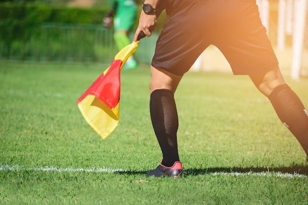 Voetbalscheidsrechter, de assistent-scheidsrechter houdt toezicht op de voetbalregels.