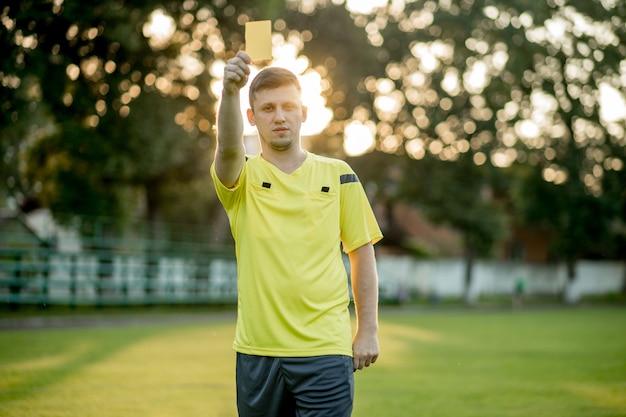 Voetbalscheidsrechter wijst een speler in het voetbalstadion op een gele kaart