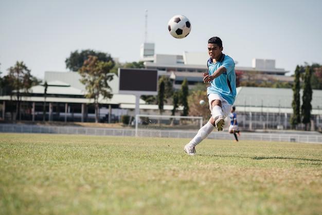 Voetbalspeler raakt een bal met stadion achtergrond