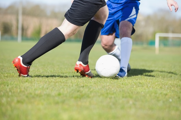 Voetbalspelers die voor de bal op hoogte aanpakken