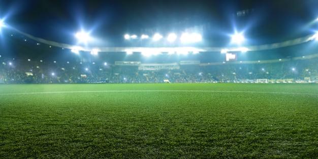 Voetbalstadion, glanzende lichten, uitzicht vanaf veld gras. gras, niemand op de speelplaats, tribunes met gamefans in de ruimte