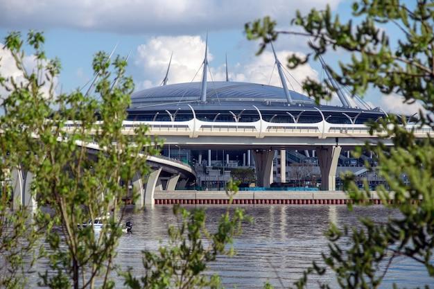 Voetbalstadion op de achtergrond van groene bomen en een rivier