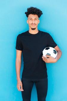 Voetbalster met bal onder wapen dichtbij muur