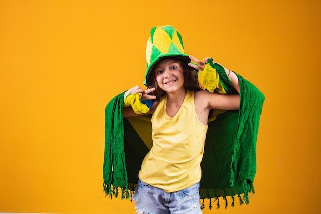 Voetbalsupporter, het team van brazilië. mooi meisje juichen voor haar team op gele achtergrond
