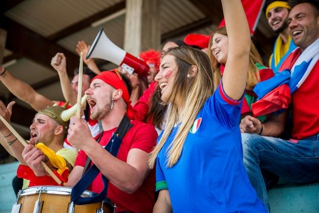 Voetbalsupporters in het stadion - voetbalfans die plezier hebben en naar voetbalwedstrijden kijken
