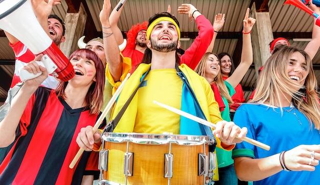 Voetbalsupporters juichen en kijken naar de voetbalbekerwedstrijd op de tribunes van het internationale stadion