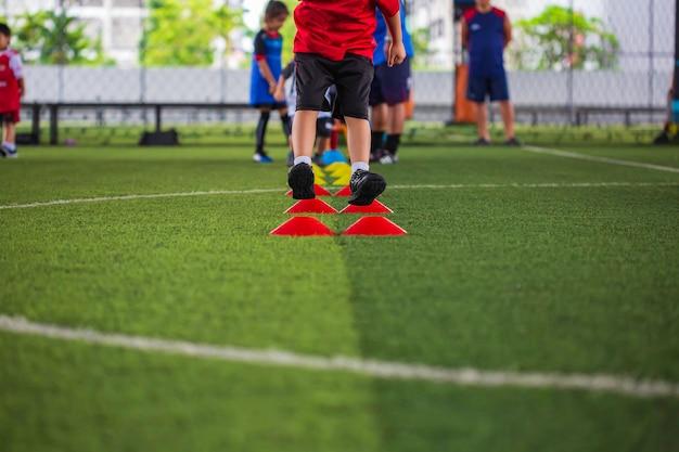 Voetbaltactieken op grasveld met barrière voor het trainen van kinderen springvaardigheid in voetbalacademie