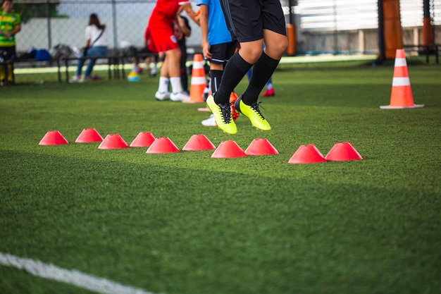 Voetbaltactieken op grasveld met barrièrekegel voor het trainen van de springvaardigheid van kinderen in de voetbalacademie
