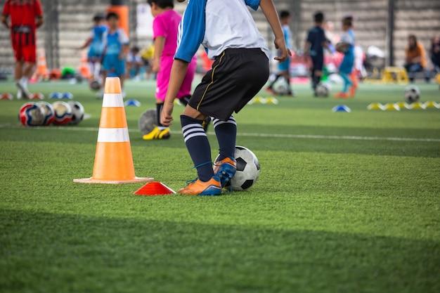 Voetbaltactieken op grasveld met kegel voor trainingsachtergrond kinderen opleiden in voetbalacademie