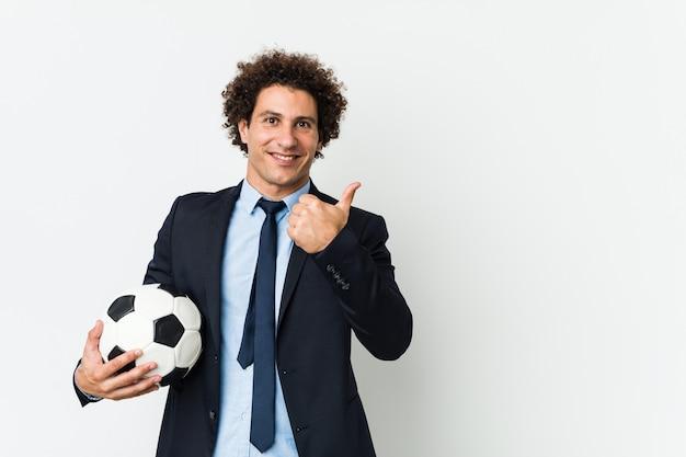 Voetbaltrainer die een bal houden glimlachend en duim opheffend