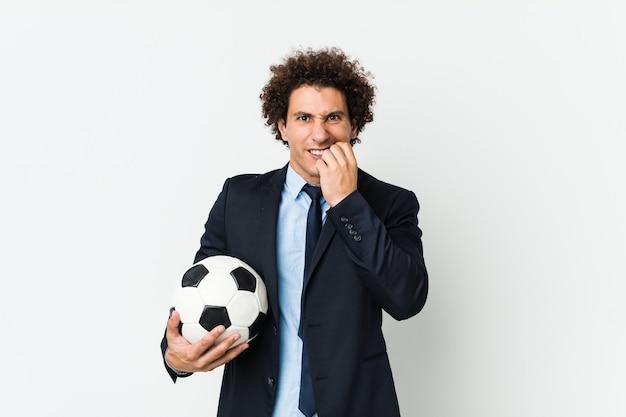 Voetbaltrainer die een bal vasthoudt die nagels bijt, nerveus en erg angstig