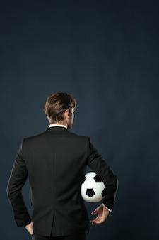 Voetbaltrainer in zwart pak met een bal