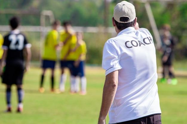 Voetbaltrainer met wit coach-shirt op een sportveld buiten zijn team coachend