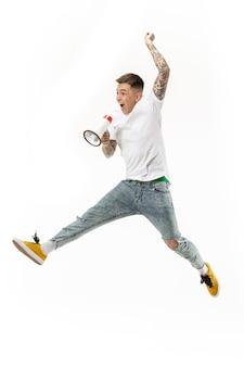 Voetbalventilator die op witte achtergrond springt. de jonge man als voetbalfan met megafoon geïsoleerd op oranje studio.