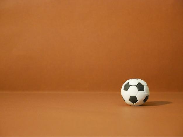 Voetbalvoetbal met exemplaarruimte op bruine achtergrond.