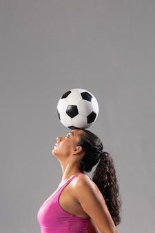 Voetbalvrouw die trucs met bal doen