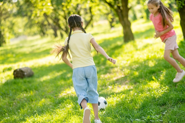 Voetbalwedstrijd. twee energieke geïnteresseerde langharige meisjes lopen met voetbal op groen gras in het park op zomerdag