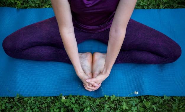 Voeten en handen van een meisje, zittend op een tapijt en mediteren in de natuur
