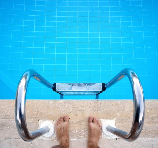 Voeten in de buurt van trappen naar het zwembad