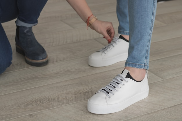 Voeten in jeans en witte sneakers