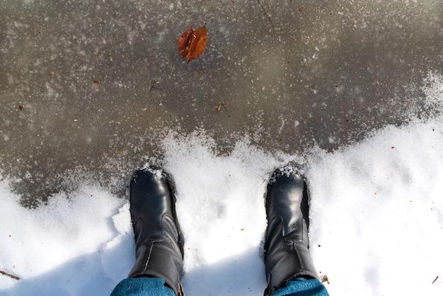 Voeten in laarzen in een bevroren plas