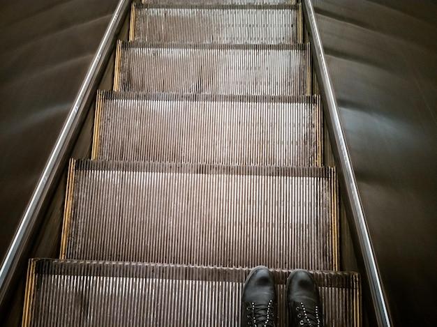 Voeten in laarzen op de roltrap bovenaanzicht mens rijdt een roltrap door de metro