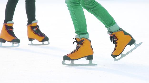 Voeten in rode schaatsen op een ijsbaan. hobby's en sporten tijdens de wintervakantie