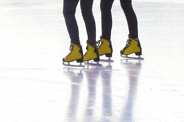 Voeten in rode schaatsen op een ijsbaan. sporten en amusement. rust- en wintervakanties.