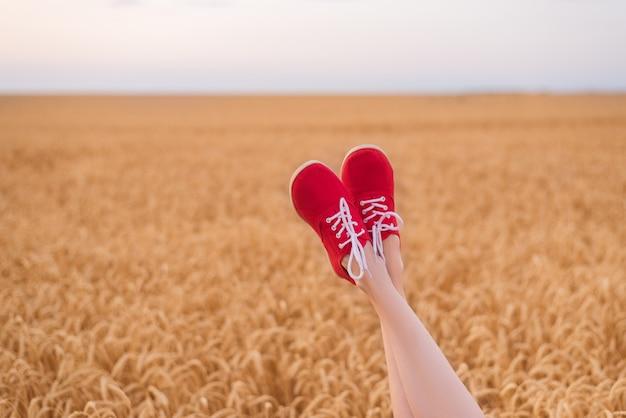 Voeten in rode schoenen grappig steken uit tarweveld. blijf jezelf.