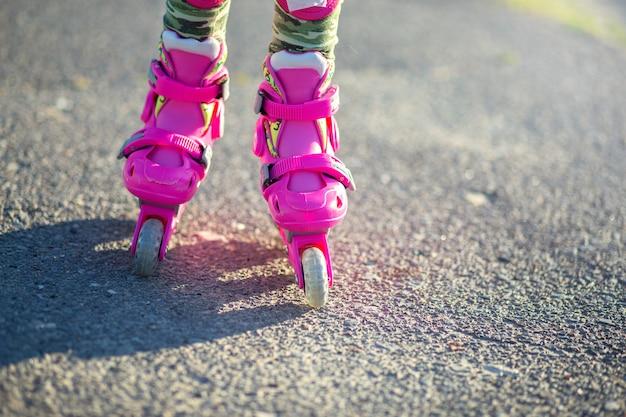 Voeten in roze kinderen rollen close-up.