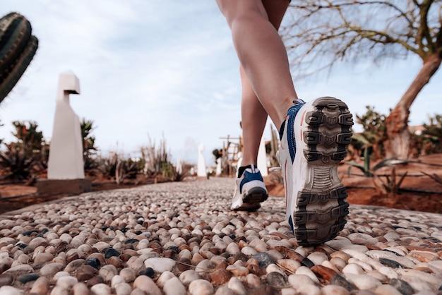 Voeten in sneakers op een rotsachtige weg