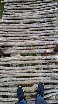 Voeten in zwarte sneakers op een houten brug