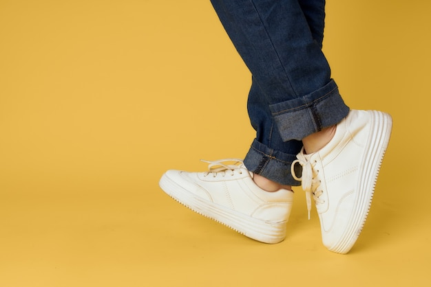 Voeten jeans mode schoenen witte sneakers gele achtergrond