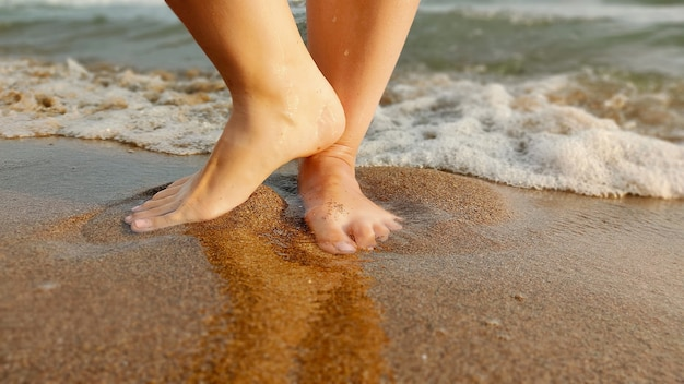 Voeten kleine baby op het zand met watergolf van het overzeese strand. zomervakantie