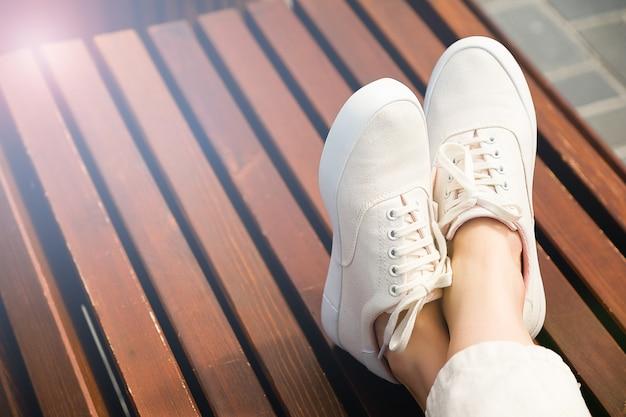 Voeten meisje in witte schoenen op een bank in het park. detailopname.