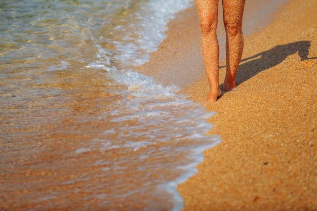 Voeten meisje op het strand. golven die naar de kust lopen
