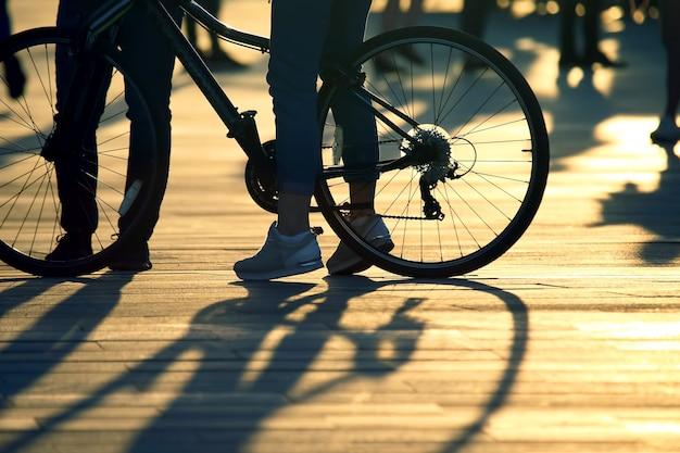 Voeten met fiets en mensen achter de ondergaande zon. vriendschap en relaties tussen mensen. sociaal gedrag in de samenleving. vrije tijd en rust.
