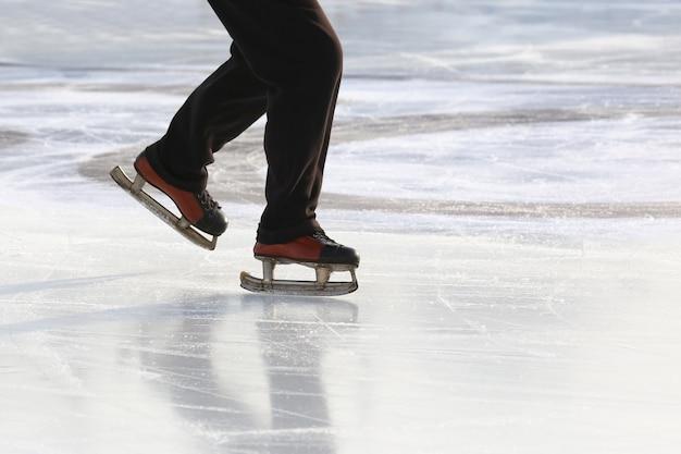 Voeten op de schaatsen van een persoon die op de ijsbaan rolt