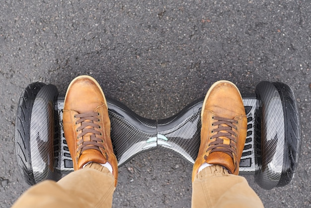 Voeten op elektrische scooter buiten, bovenaanzicht