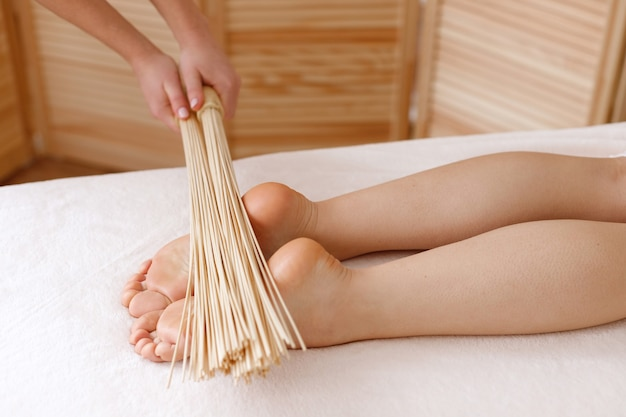 Voeten op massage met stokjes in de salon