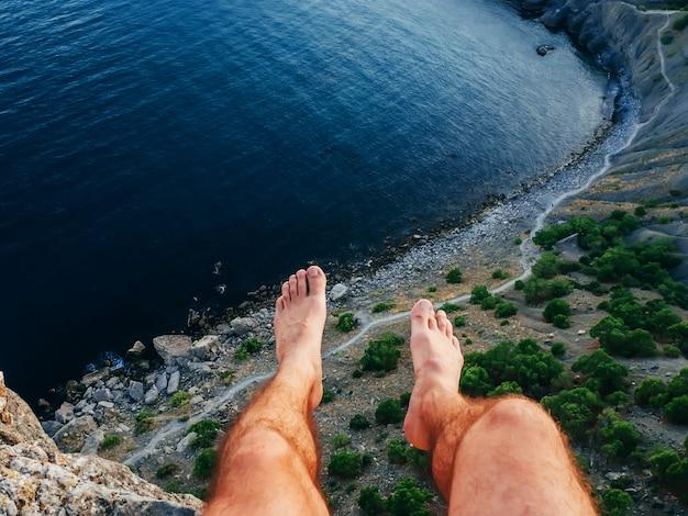 Voeten opknoping van een klif met de zee op de achtergrond