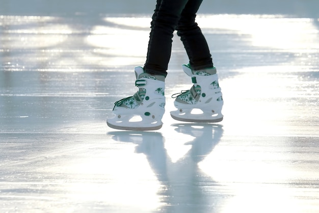 Voeten schaatsend meisje schaatsen op ijsbaan. sporten en amusement. rust- en wintervakanties.